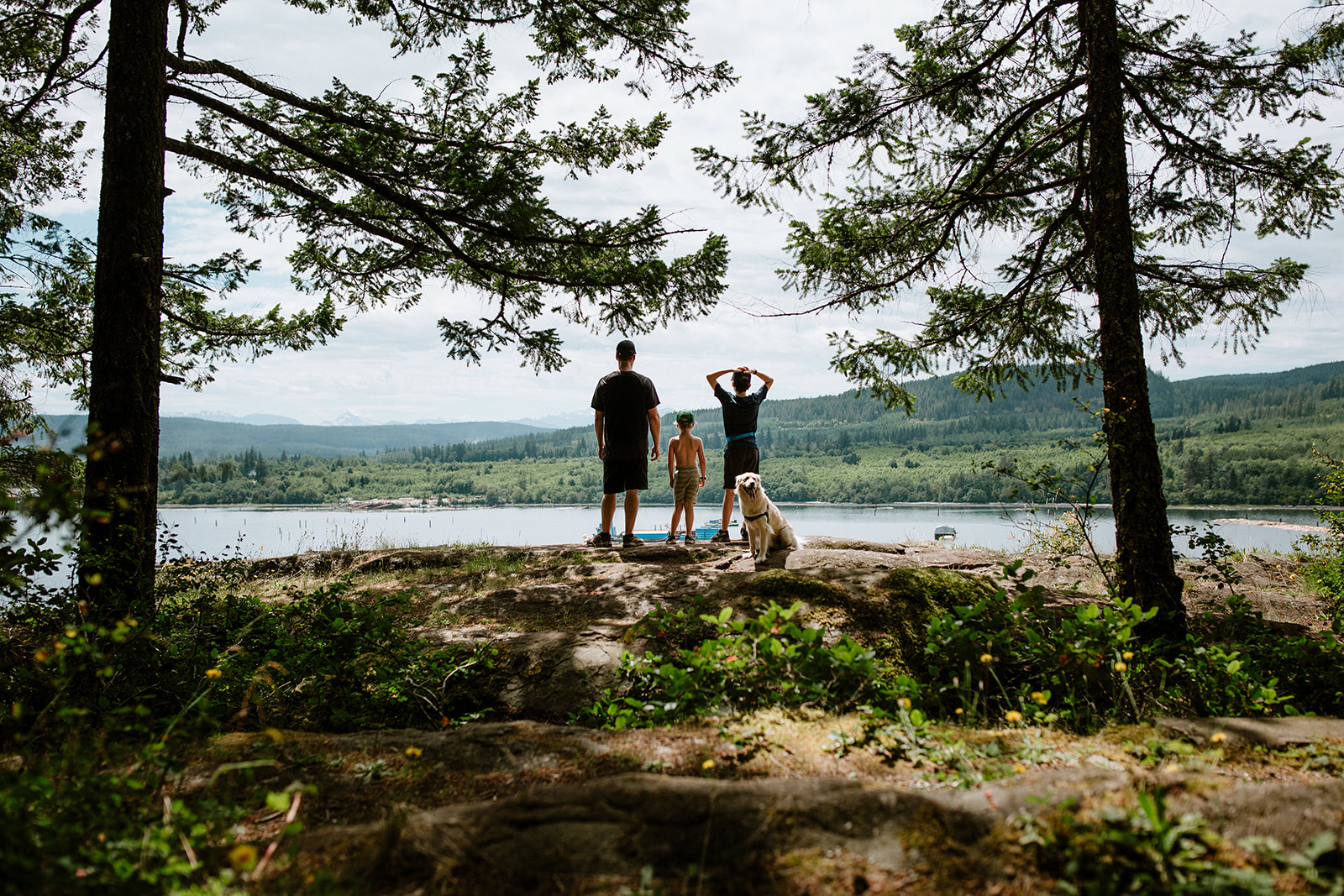 A family of 3 standing at the Ripple Rock View Point