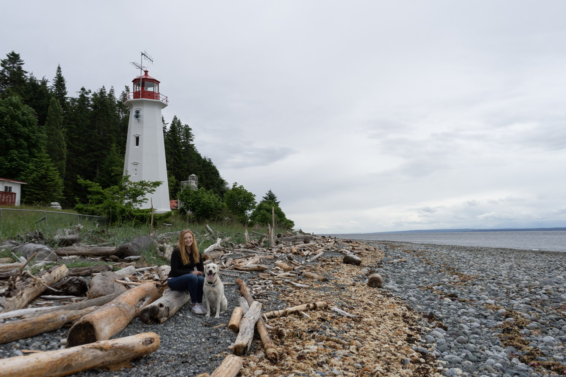 a woman and her dog sit on the beach with the Cape Mudge Lighthouse behind them